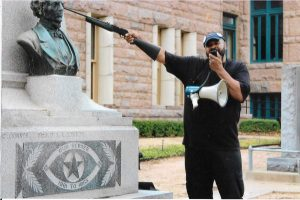 A protestor points a gun at a Confederate monument in Lamar County, TX.